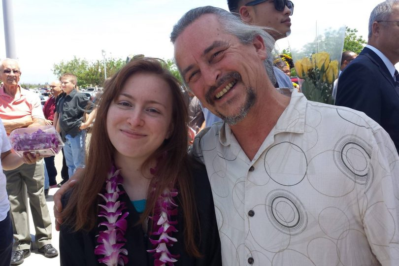 Josie Perez in a black graduation robe with a flower lei around her neck, with her father Mike Perez, on graduation day 2014 as she receives her bachelor's degree in English.
