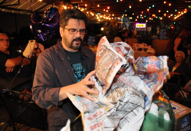Photo of Raul Perez at his 50th Birthday Party, opening presents.